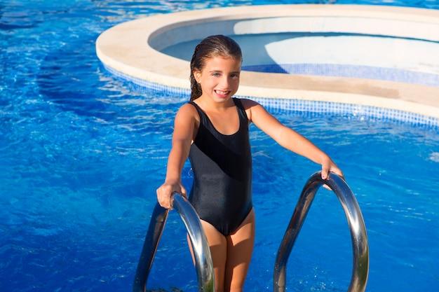Kindermädchen auf dem blauen schwarzen badeanzug der pooltreppe