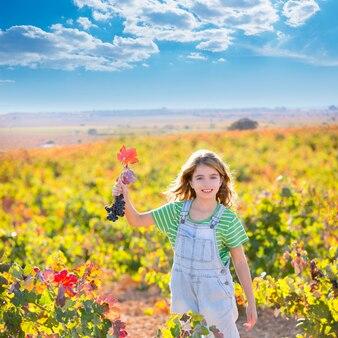 Kindermädchen auf dem herbstweinberggebiet, das bündel der roten trauben hält