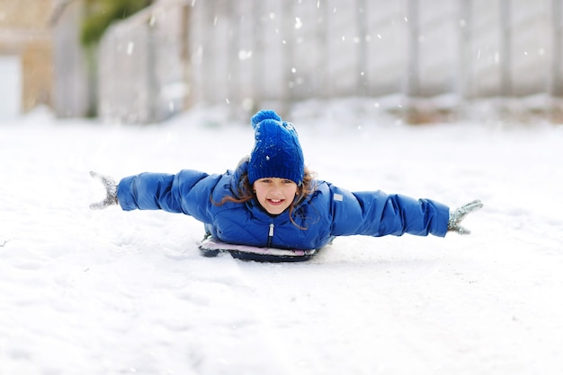Kindermädchen auf schneeröhren bergab am wintertag