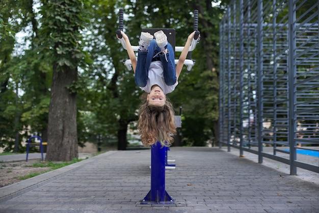 Kindermädchen auf sport-outdoor-simulator, kopfüber hängend, aktiver gesunder lebensstil von kindern, städtische sportplätze
