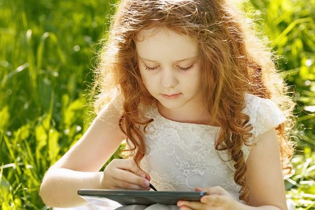 Kindermädchen, das auf gras sitzt und tabletten-pc spielt