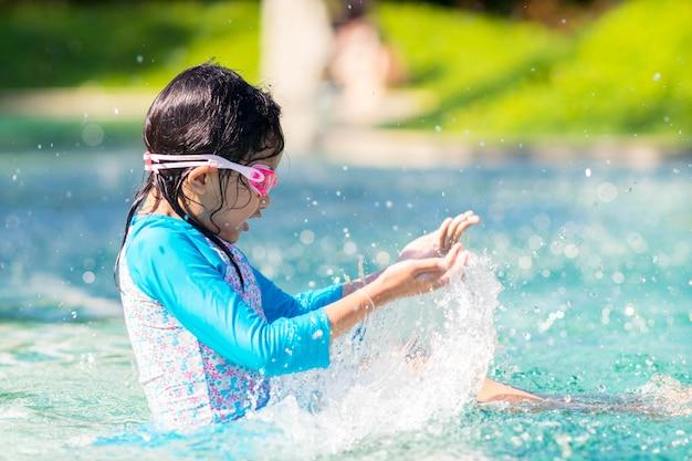 Kindermädchen, das auf swimmingpool mit glücklichem spritzt.