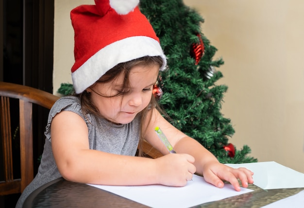 Kindermädchen, das den brief nahe dem weihnachtsbaum schreibt