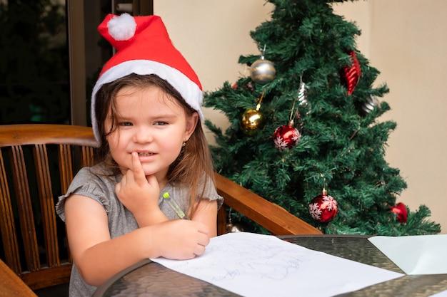 Kindermädchen, das den weihnachtsbrief nahe dem weihnachtsbaum schreibt