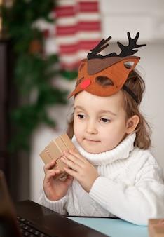 Kindermädchen, das eine geschenkbox hält und ein digitales tablet-laptop-notizbuch verwendet