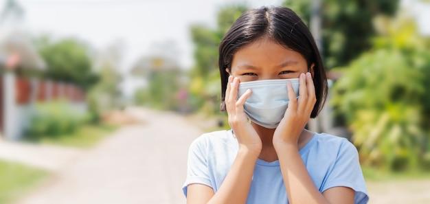 Kindermädchen, das gesichtsmaske trägt, schützt vor luftverschmutzung und virusepidemie von covid 19