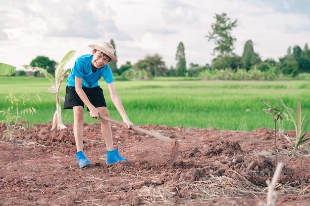 Kindermädchen, das hacke hält und erde zum pflanzen von bäumen im garten gräbt