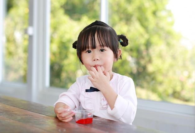 Kindermädchen, das ihre finger beim essen leckt.