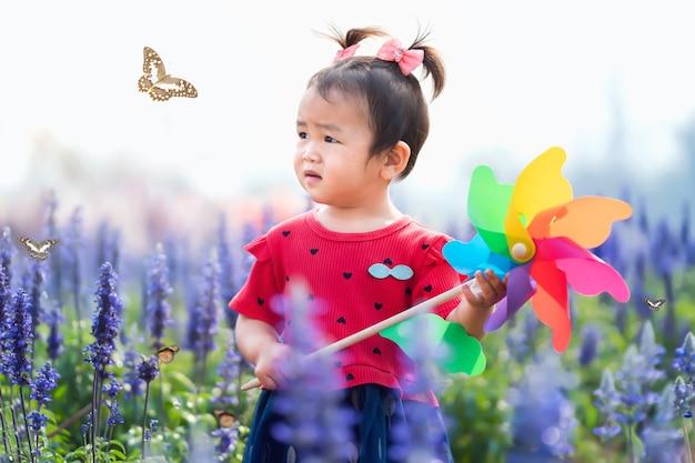 Kindermädchen, das im blumengarten steht und spielzeugwindmühle hält, die schmetterling betrachtet