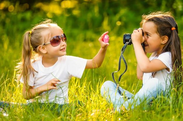 Kindermädchen, das im gras mit einer fotokamera sitzt