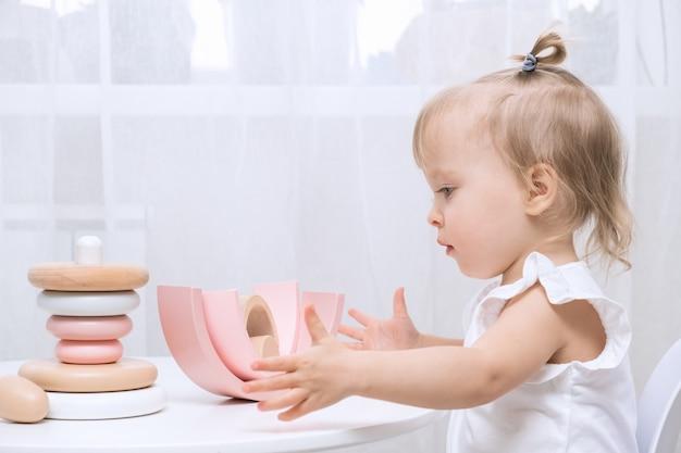 Kindermädchen, das mit einem hölzernen spielzeug am tisch spielt. kleines süßes mädchen mit natürlichem spielzeug.