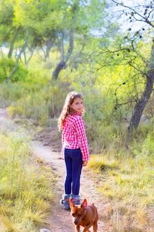 Kindermädchen, das mit hund im kiefernwald geht