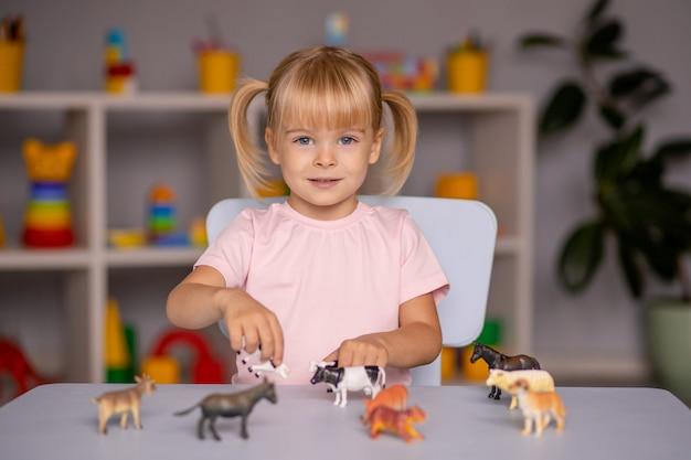 Kindermädchen, das mit spielzeugtieren am tisch im kindergarten oder zu hause spielt