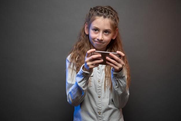 Kindermädchen, das mit telefon spielt und lächelt