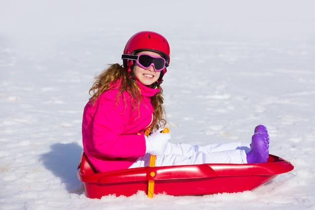 Kindermädchen, das schlitten im winterschnee spielt