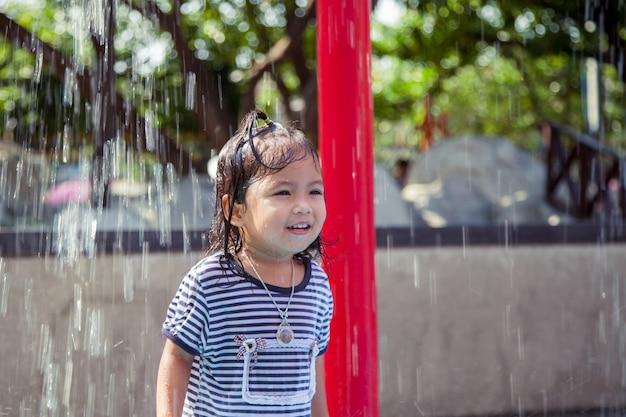 Kindermädchen, das spaß hat, mit wasser im parkbrunnen in der sommerzeit zu spielen