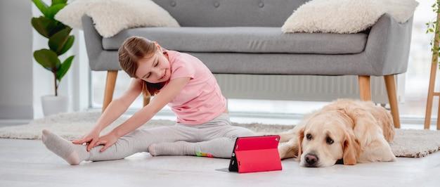 Kindermädchen, das zu hause yoga-online-training mit tablet macht, während golden retriever-hund dicht neben ihr auf dem boden liegt laying