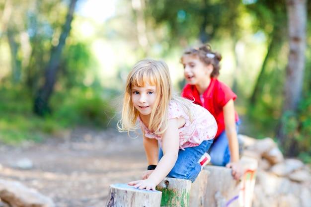 Kindermädchen, die auf stämmen in der waldnatur spielen