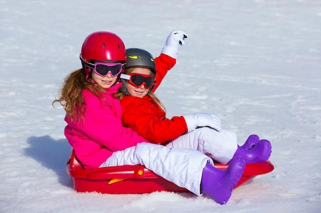 Kindermädchen, die schlitten im winterschnee spielen