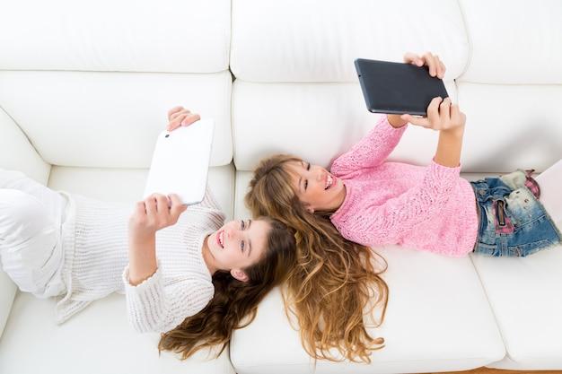 Kindermädchen, die spaß haben, mit liegendem sofa des tabletten-pc zu spielen