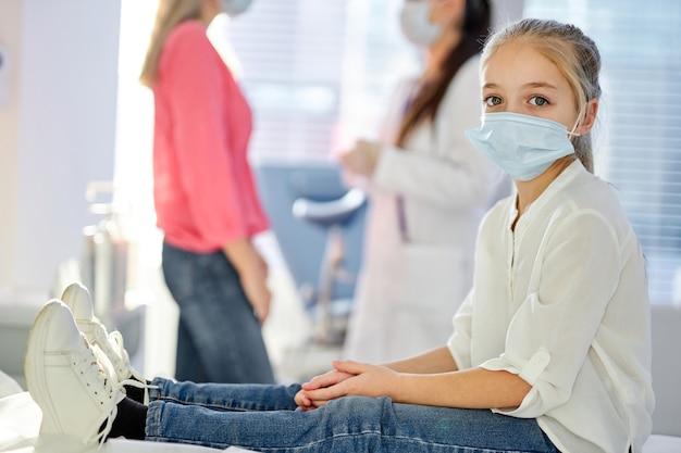 Kindermädchen in der medizinischen maske, die kamera betrachtet, auf bett im krankenhaus oder in der klinik sitzend, während ihre elternmutter mit krankenschwester im hintergrund spricht