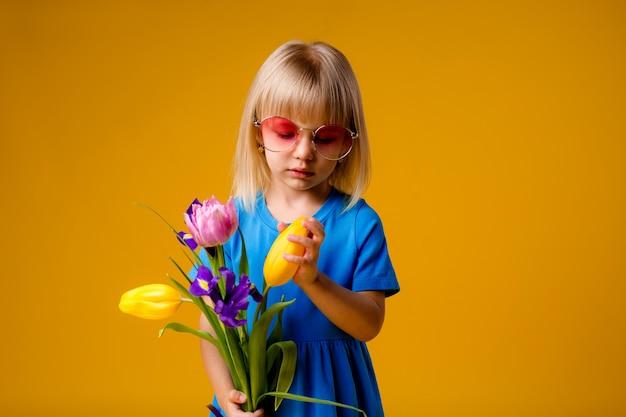 Kindermädchen in der sonnenbrille in den blauen kleidern, die lächeln und einen blumenstrauß auf einem gelben hintergrund des isolats halten