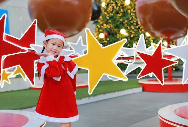 Kindermädchen in sankt-hut wirft und spaß zur weihnachtszeit auf. frohe weihnachten hintergrund.