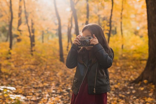 Kindermädchen mit einer altmodischen kamera im herbst naturfotograf herbstsaison und freizeit