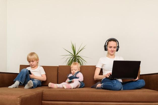 Kindermädchen mit laptop zum surfen im internet, während kinder mit telefonen spielen. schlechtes kindermädchen-konzept