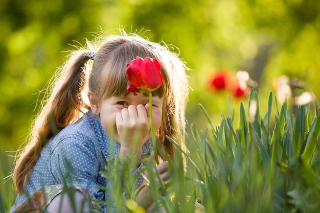Kindermädchen mit roter tulpenblume.