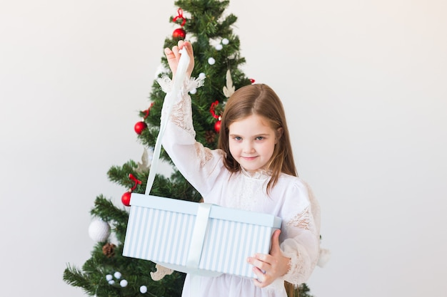 Kindermädchen öffnet geschenkbox nahe weihnachtsbaum