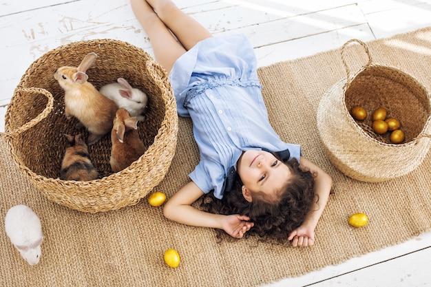 Kindermädchen schön süß fröhlich und glücklich mit kleinen tieren kaninchen und ostereiern zu hause