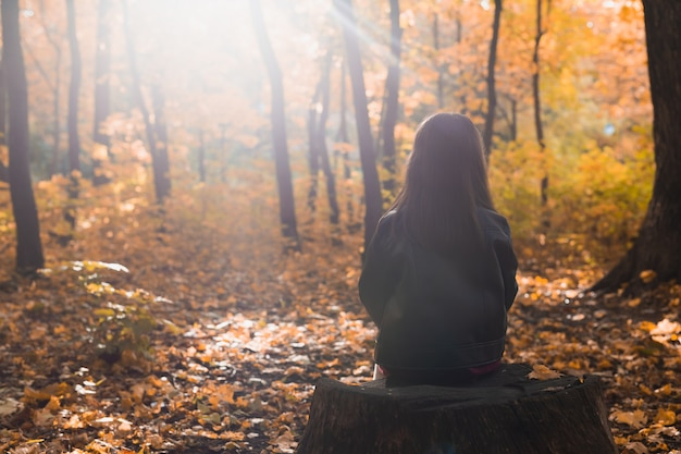 Kindermädchen sitzt allein auf einem holzstumpf beim spaziergang durch den wald an einem herbsttag einsamkeit