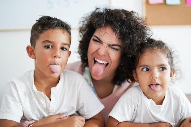 Kindermädchen und kinder machen lustigen gesichtsausdruck vor der kamera - kindertagesstätte und glückskonzept