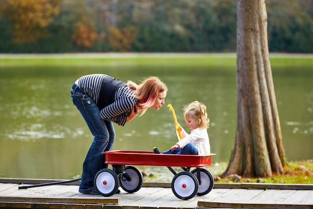 Kindermädchen und -mutter, die im see mit zugwagen spielen