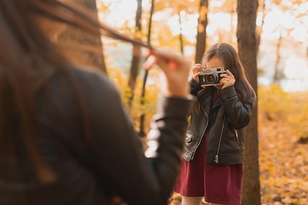 Kindermädchenfotograf fotografiert eine mutter im park im herbst hobbys fotokunst und