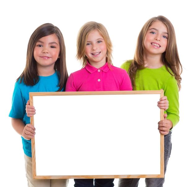 Kindermädchengruppe, die leeren kopienraum des weißen brettes hält