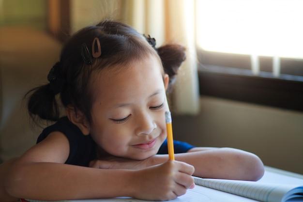 Kindermädchenschreiben auf dem buch mit lächeln.