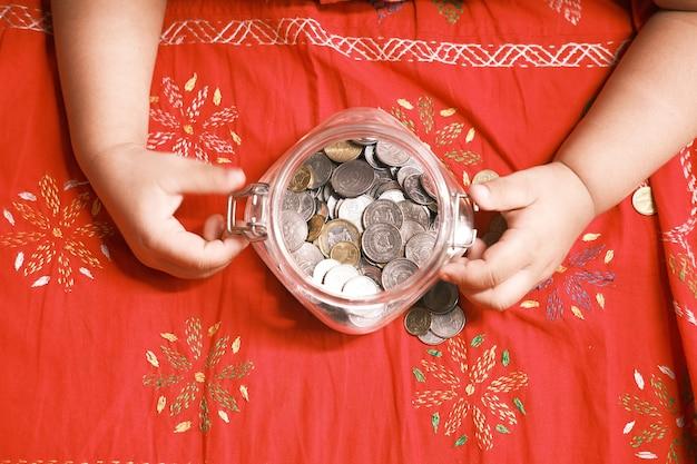 Kindermädchenstapelmünze zum speichern auf der draufsicht des bettes