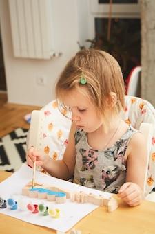 Kindermalerei. glückliches mädchen im vorschulalter, das einen pinsel hält