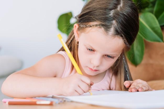 Kindermalerei hobby. kunstvolle kinder freizeit. fokussiertes kleines mädchen, das ihre fantasie auf papier zeichnet und ausdrückt.