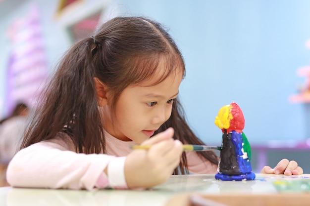Kindermalerei, kleines mädchen des porträts, das den spaß hat, auf der stuckpuppe innen zu malen.