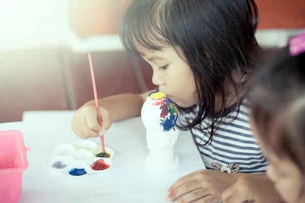 Kindermalerei, nettes kleines mädchen, das spaß hat, auf stuckpuppe zusammen zu malen