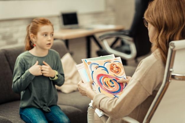 Kindermalerei. selektiver fokus einer professionellen psychologin, die ein kindergemälde hält