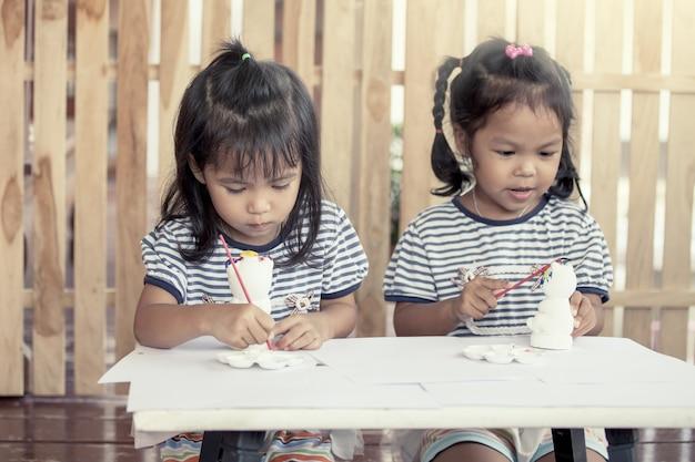 Kindermalerei, zwei kleine mädchen, die spaß haben, auf stuckpuppe zusammen zu malen