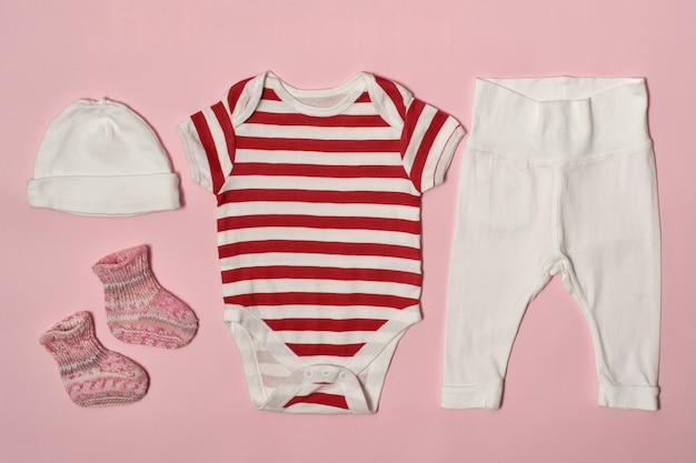 Kindermode auf einem rosa. mütze, body, hose und socken.