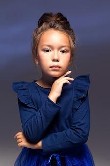 Kindermode. ein hübsches siebenjähriges mädchen in jacke, leggings und blauer schleppe posiert auf dunklem hintergrund. ein studiofoto. mode