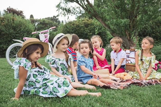 Kindermode-konzept. die gruppe von jugendlichen jungen und mädchen, die am grünen gras im park sitzen.