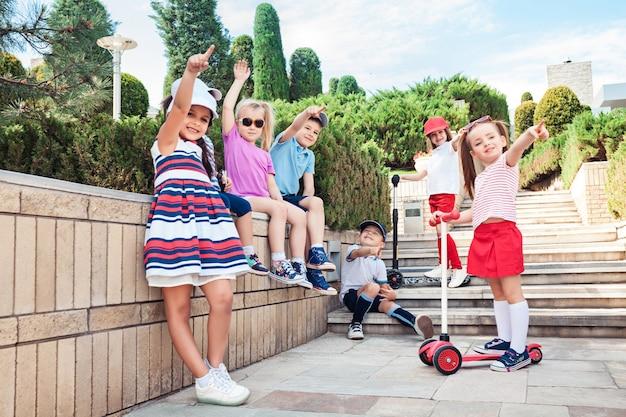 Kindermode-konzept. die gruppe von jugendlichen jungen und mädchen, die im park posieren. kinder bunte kleidung, lebensstil, trendige farbkonzepte.