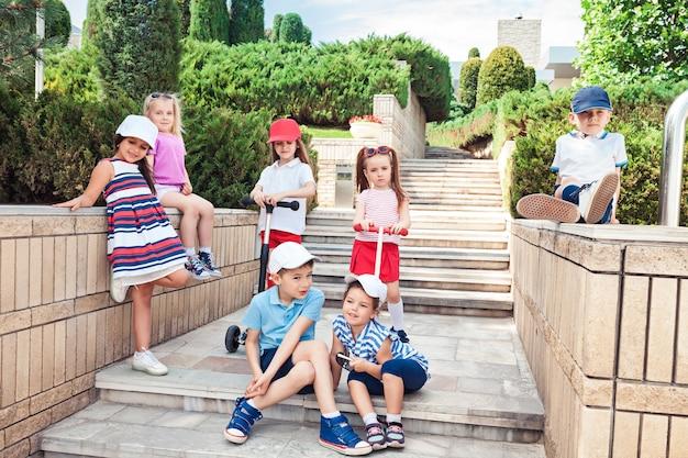 Kindermode-konzept. gruppe von jugendlich jungen und mädchen, die am park aufwerfen. kinder bunte kleidung, lebensstil, trendige farbkonzepte.